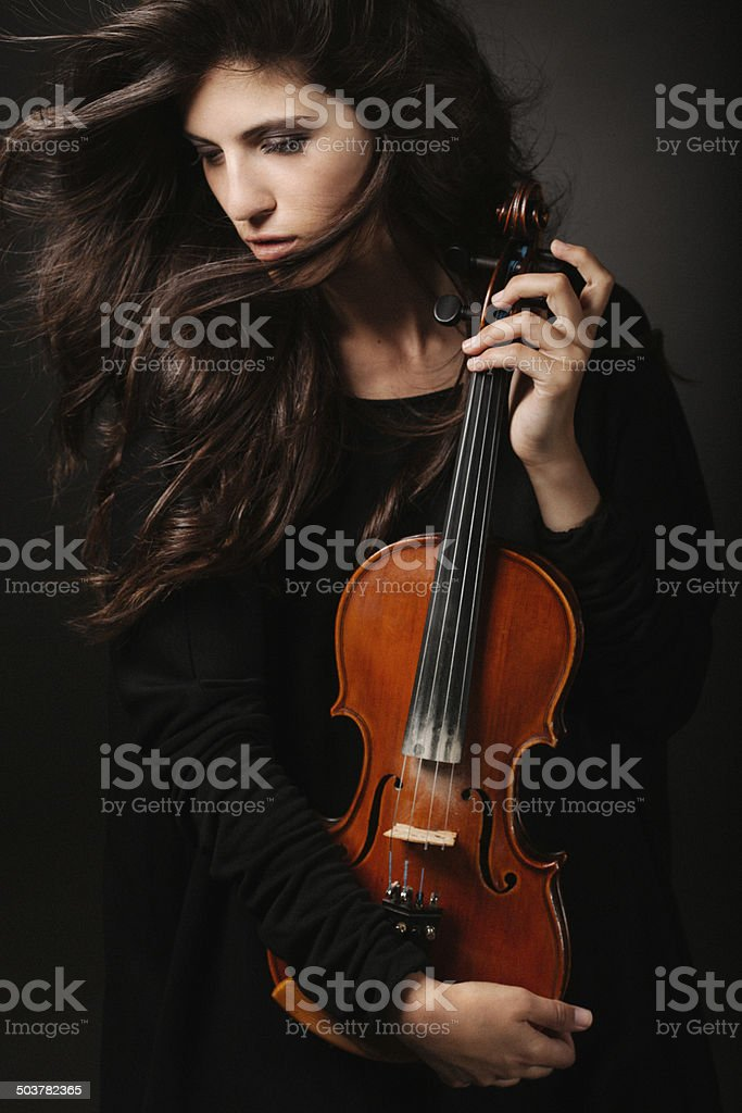 Portrait of a fresh and lovely woman holding violin stock photo