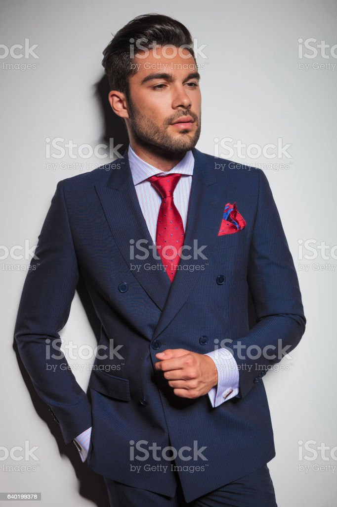 portrait of a gentleman leaning against grey wall stock photo