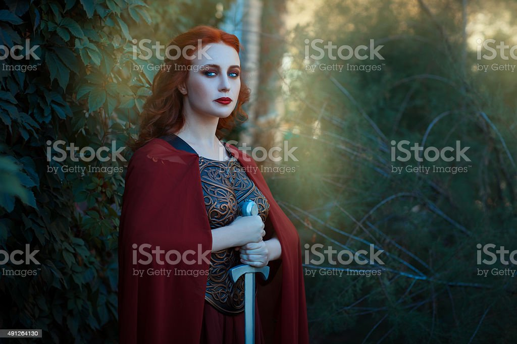 Portrait of a girl female warrior with sword in hand. stock photo