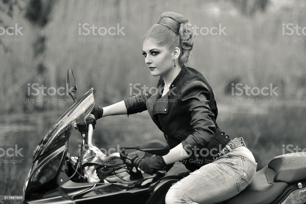 Portrait of a girl on bike,motorbike.Professional blonde biker stock photo