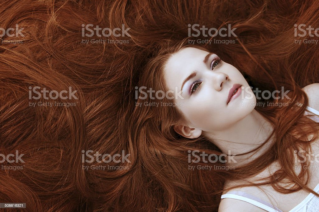 portrait of a girl with beautiful long red shiny hair stock photo