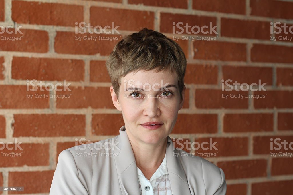Portrait of a gorgeous woman against a classic brick wall stock photo