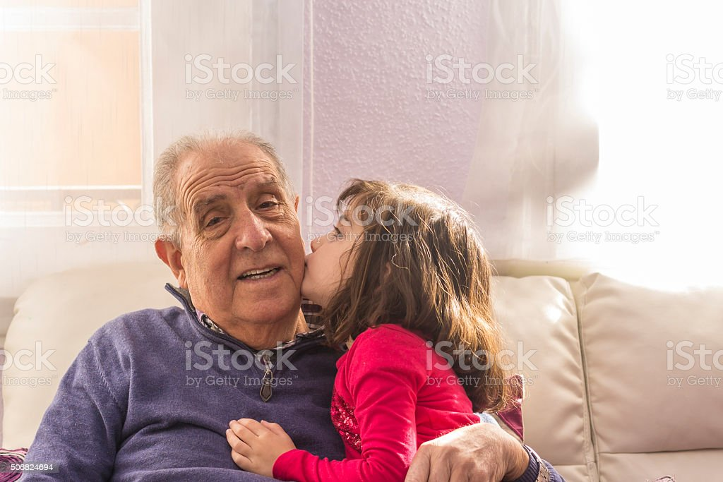 Portrait of a grandfather sitting smiling with his granddaughter stock photo
