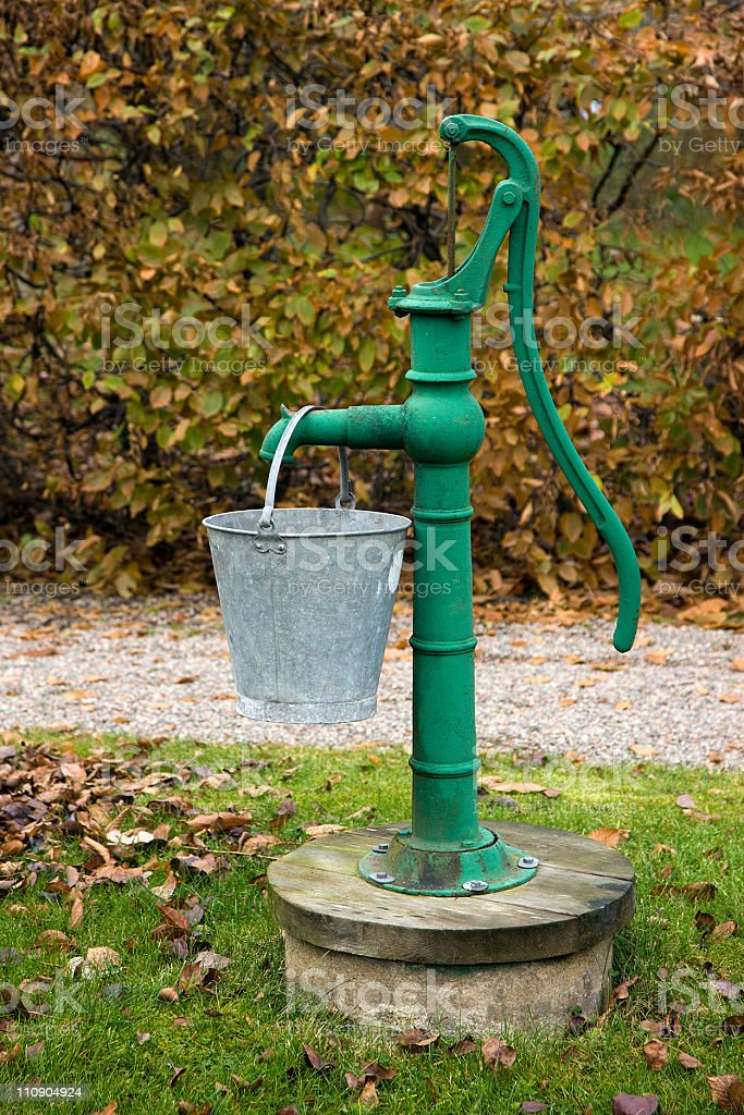 Portrait of a green water pump with a pail hanging on it stock photo