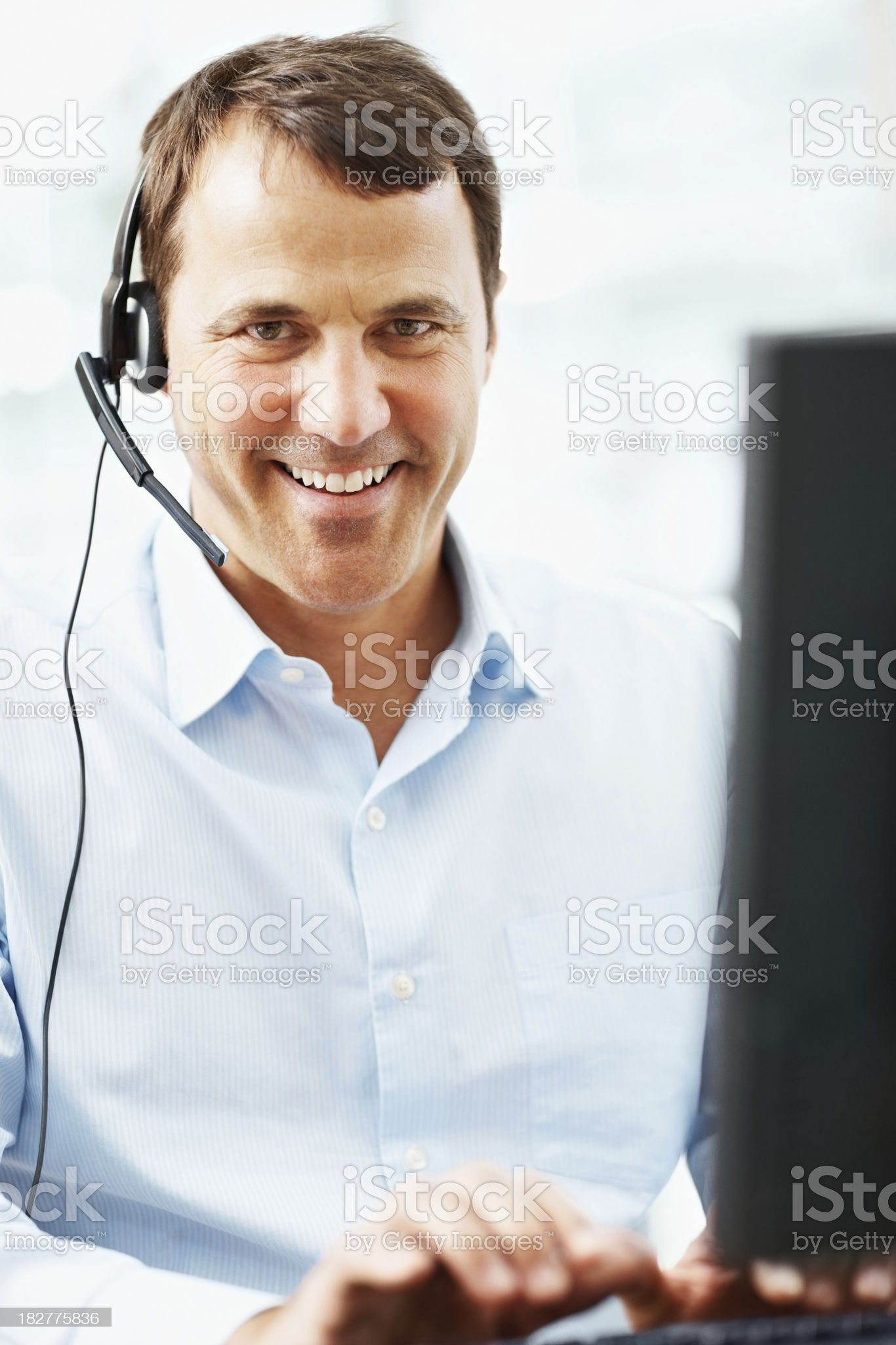 Portrait of a handsome call center employee working on computer royalty-free stock photo