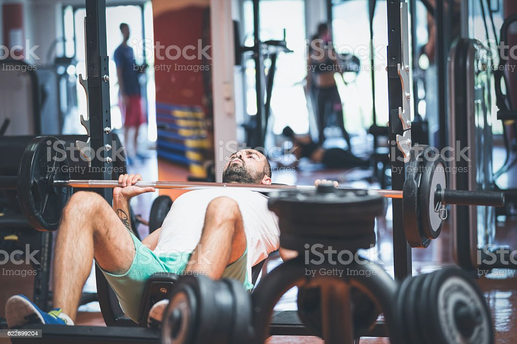 Portrait of a handsome male bodybuilder doing bench stock photo