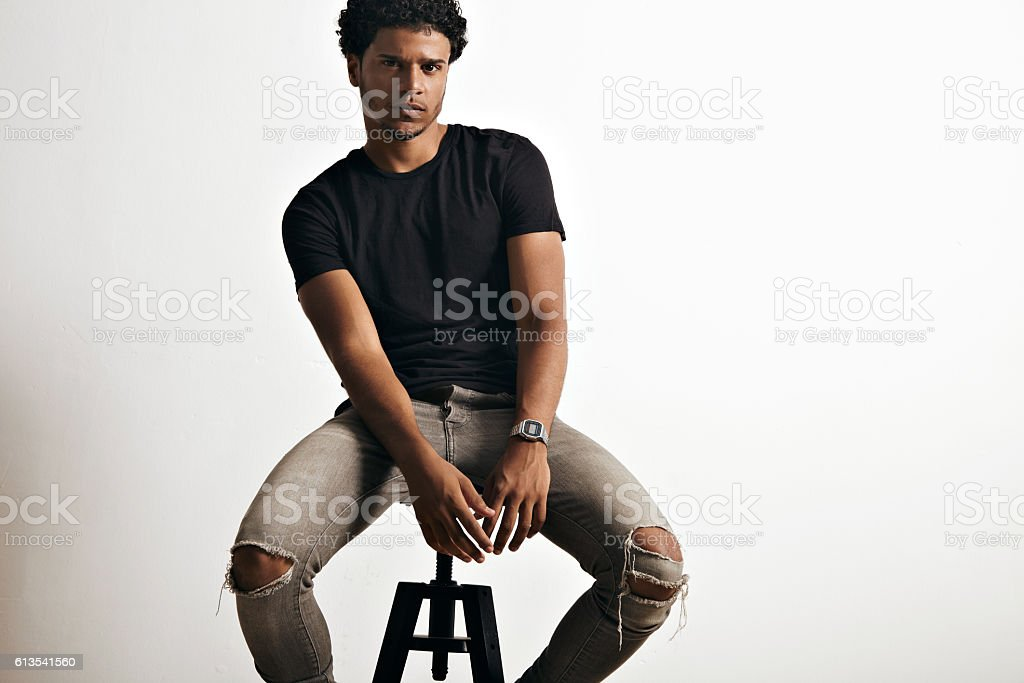 Portrait of a handsome man in black t-shirt sitting stock photo
