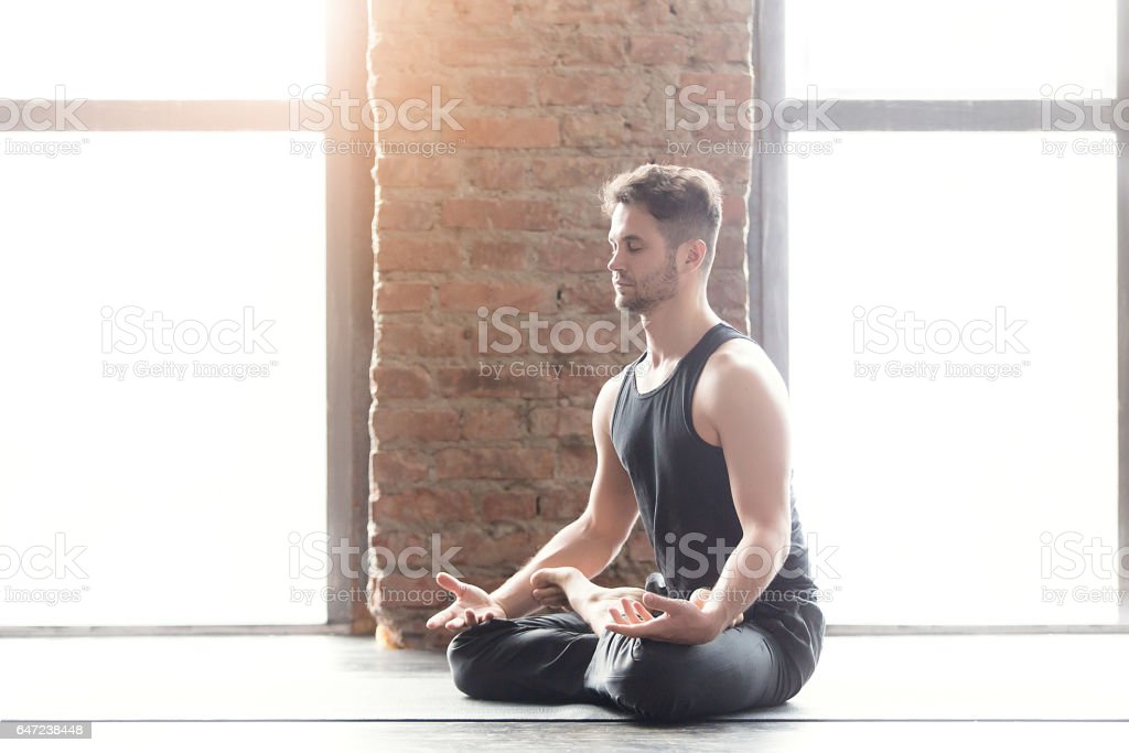 Portrait of a handsome man practicing meditation and yoga stock photo