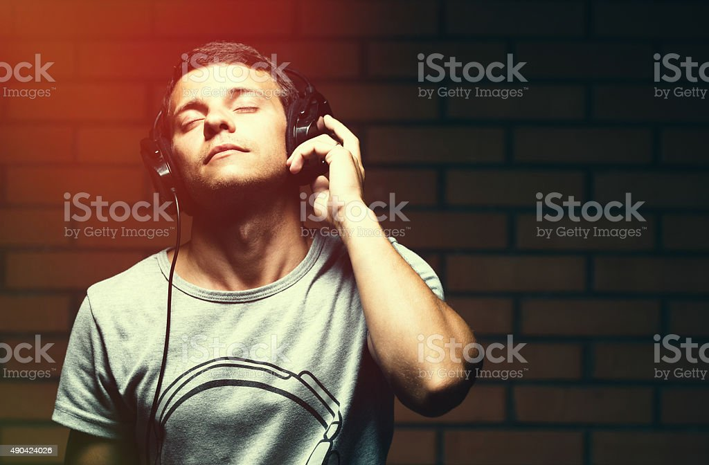 Portrait of a handsome young man listening to music stock photo