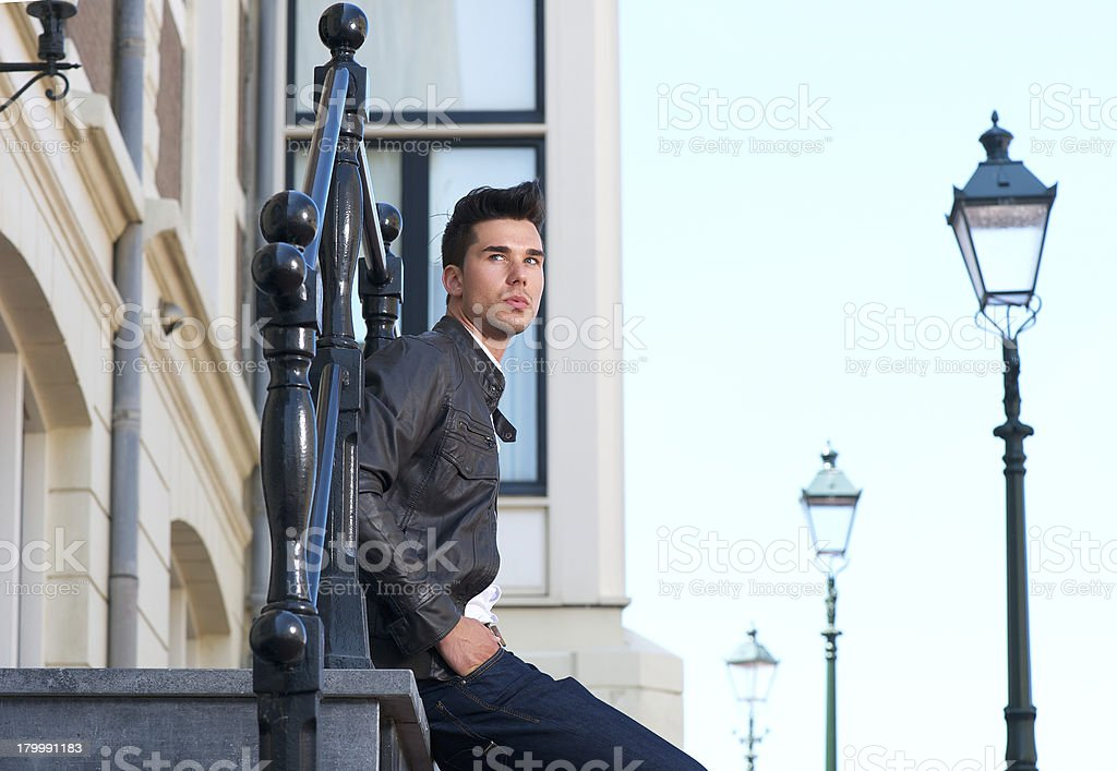 Portrait of a handsome young man sitting outdoors royalty-free stock photo
