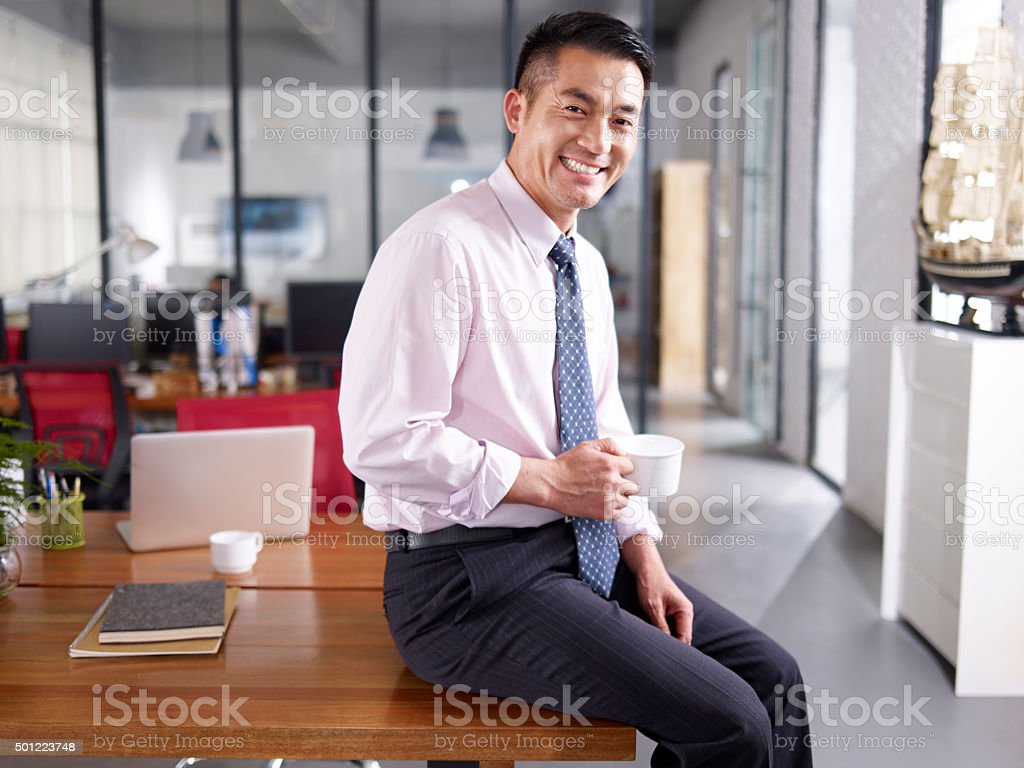 portrait of a happy asian business executive in office stock photo