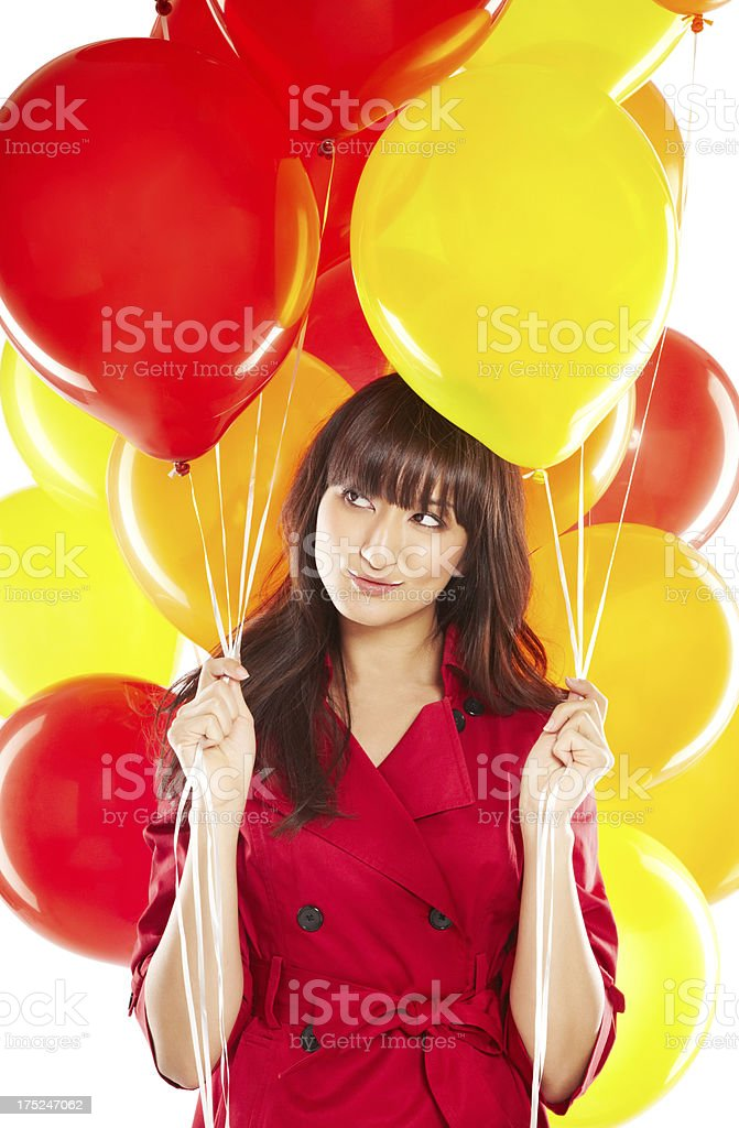 Portrait of a happy beautiful young Japanese woman holding balloons stock photo