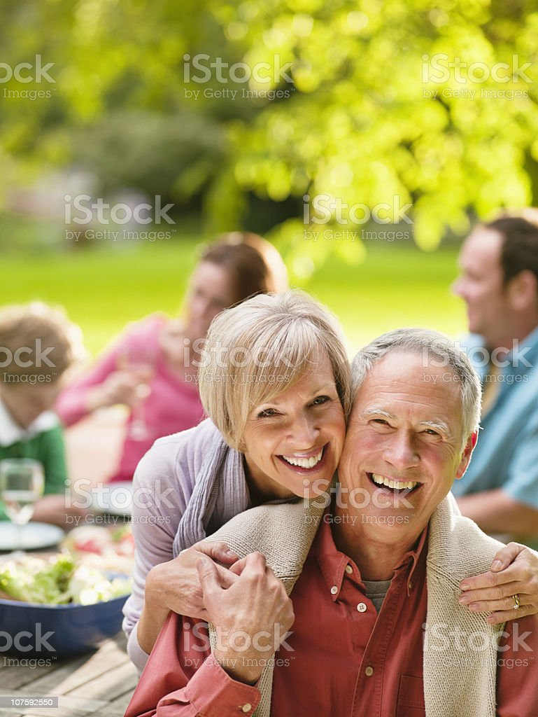 Portrait of a happy couple on picnic with family in background royalty-free stock photo