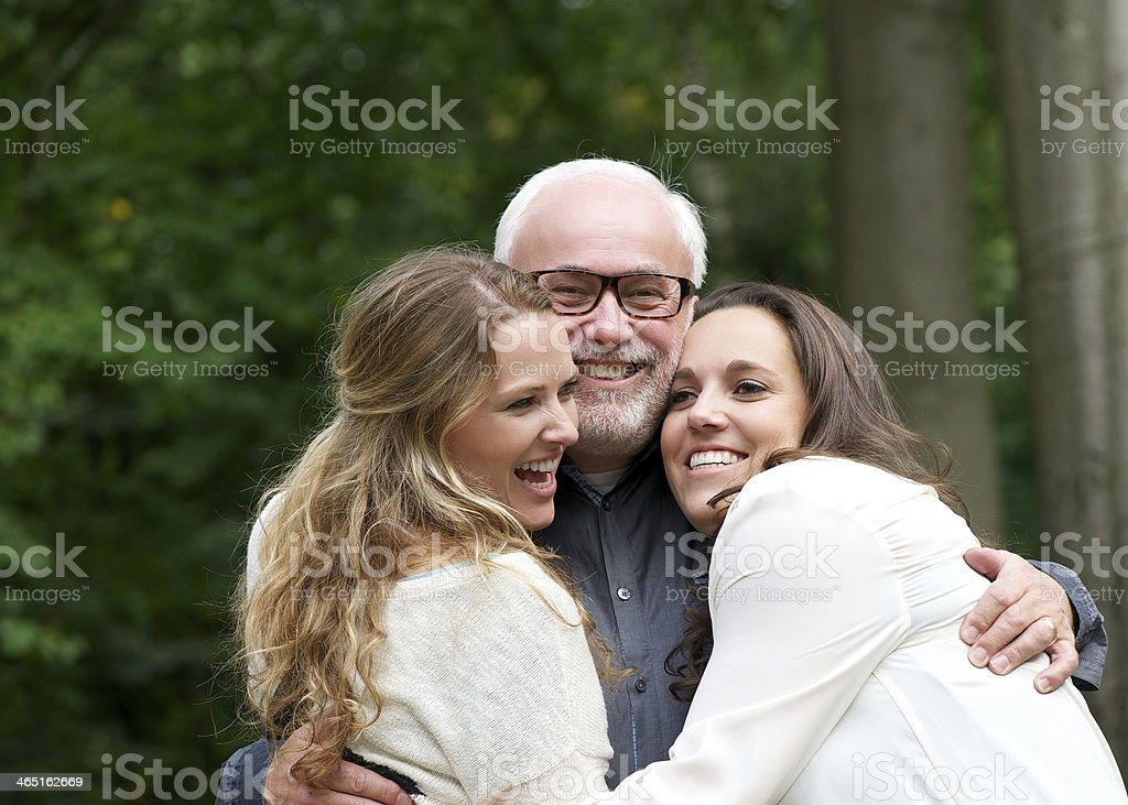 Portrait of a happy family with father and two daughters stock photo