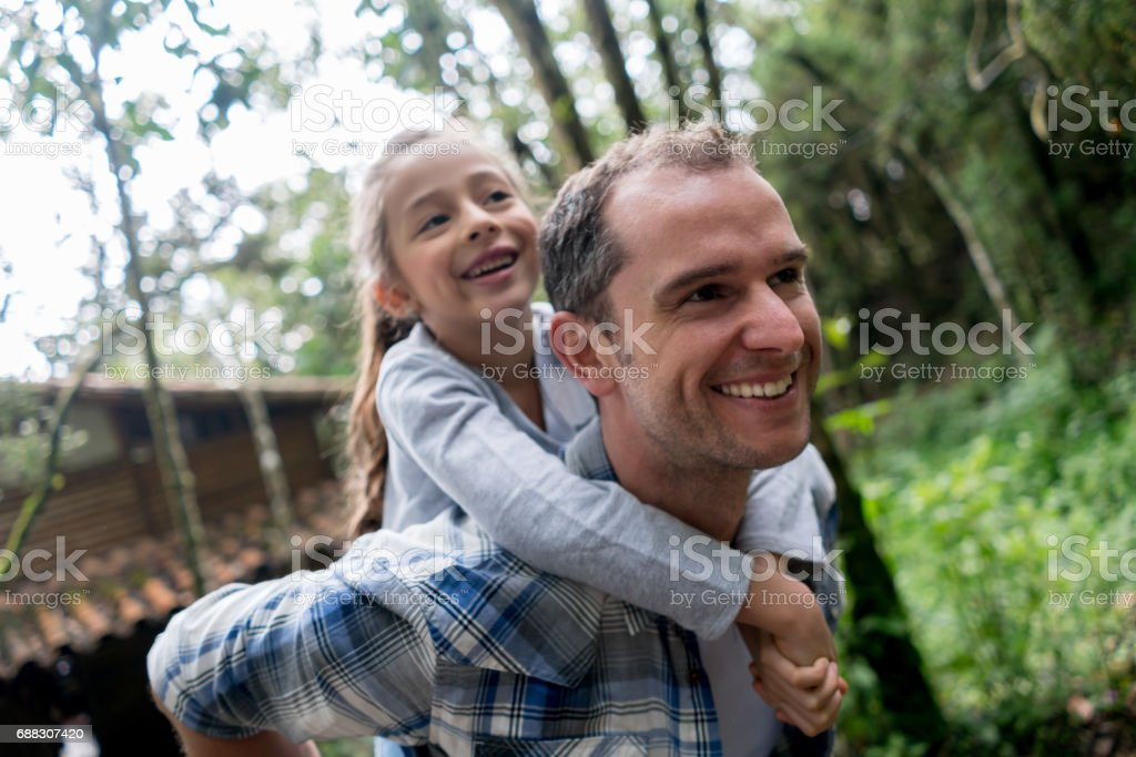 Portrait of a happy father carrying his daughter outdoors stock photo