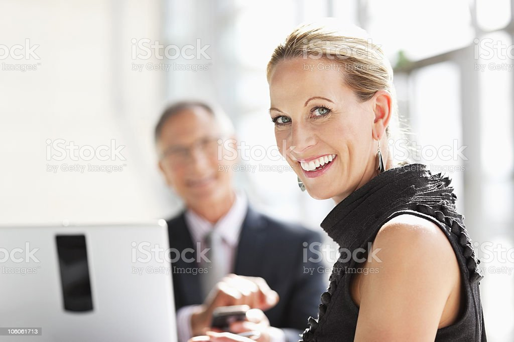 Portrait of a happy female executive with colleague in background royalty-free stock photo