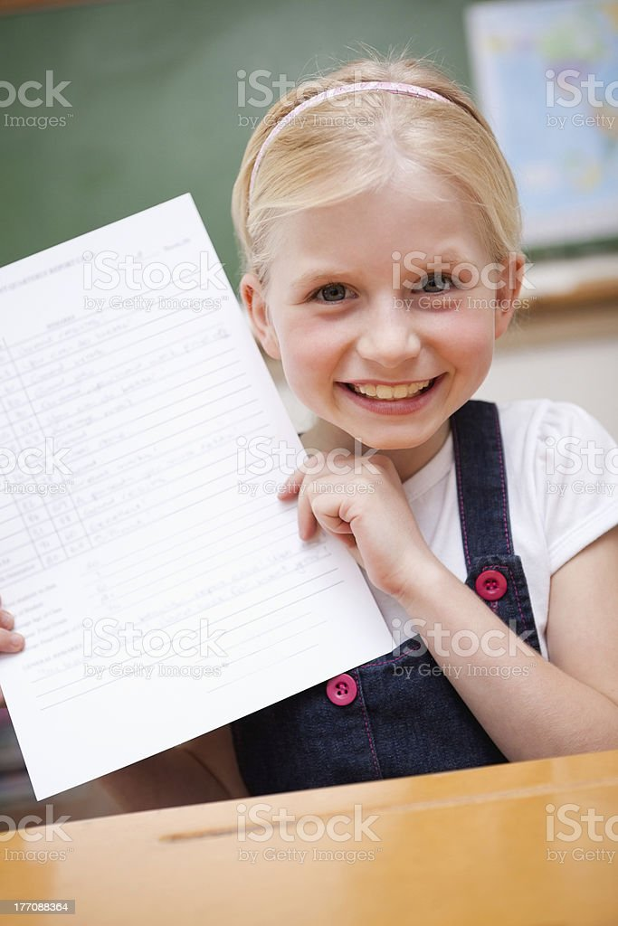 Portrait of a happy girl showing her school report royalty-free stock photo