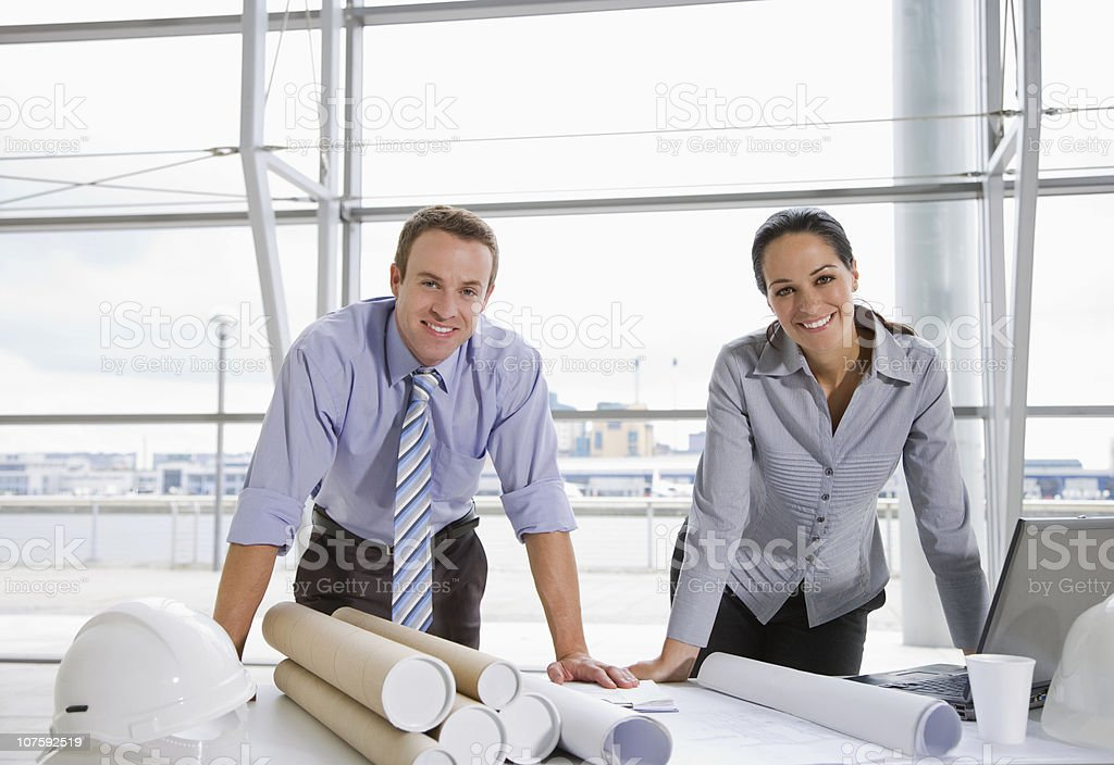 Portrait of a happy male and female architects with blue prints at office royalty-free stock photo
