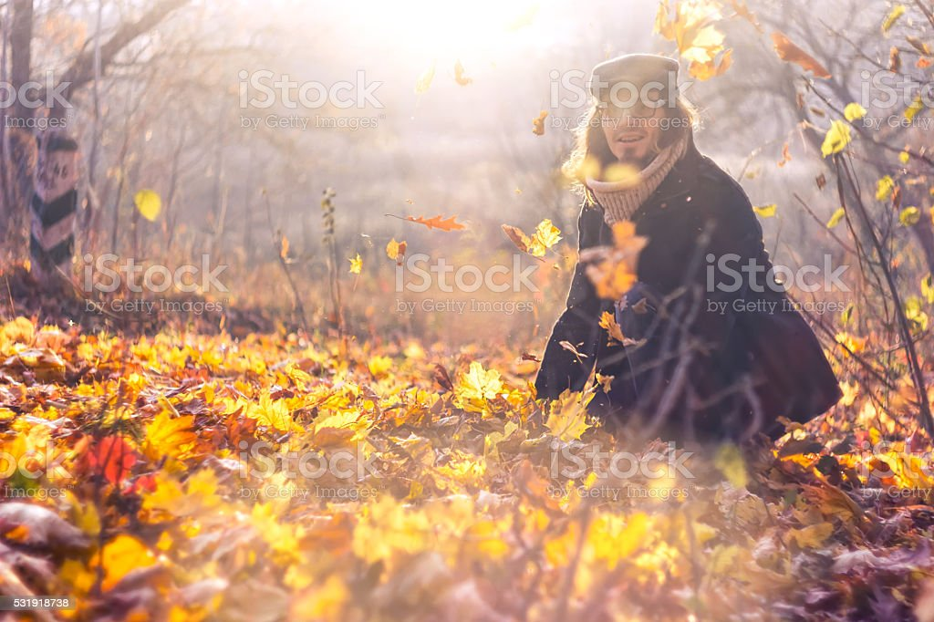 Portrait of a happy man playing with autumn leaves stock photo