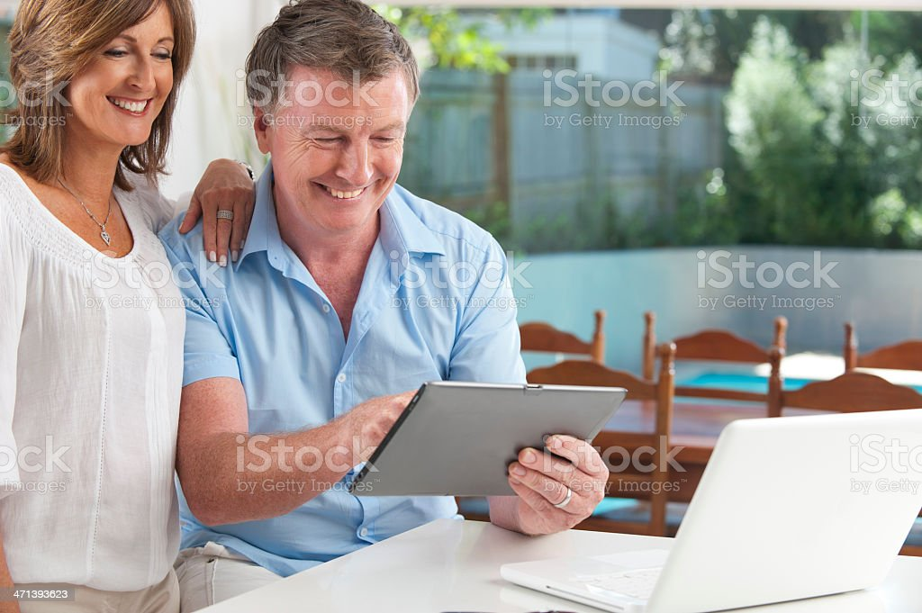 Portrait of a happy mature couple using touchpad royalty-free stock photo