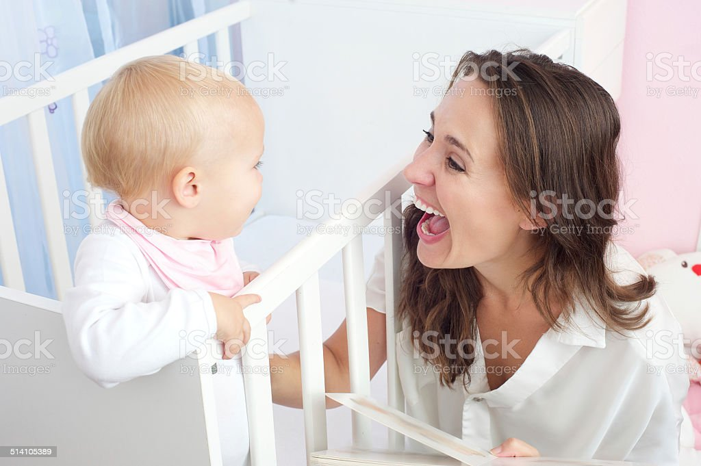 Portrait of a happy mother laughing with baby in crib stock photo