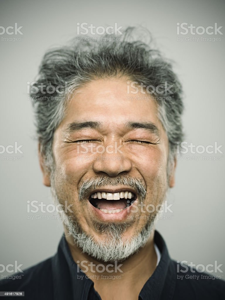 Studio portrait of a real japanese mature man with relaxed expression...