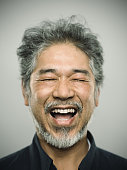 Portrait of a happy real japanese man with grey hair.