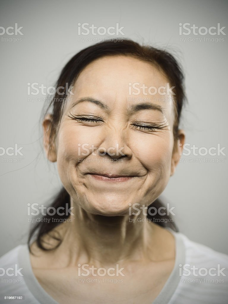 Portrait of a happy senior japanese woman with closed eyes. stock photo