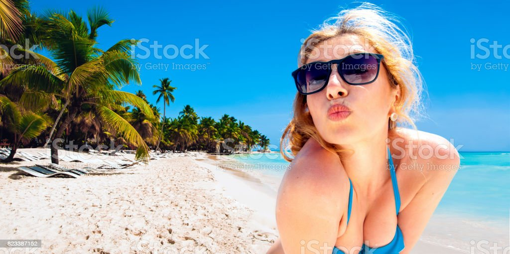 Portrait of a happy woman making an air kiss against sea view. Travel, vacation, summer holidays and happy people concept. stock photo