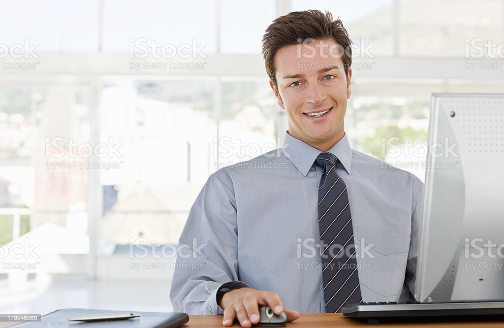 Portrait of a happy young businessman using computer royalty-free stock photo