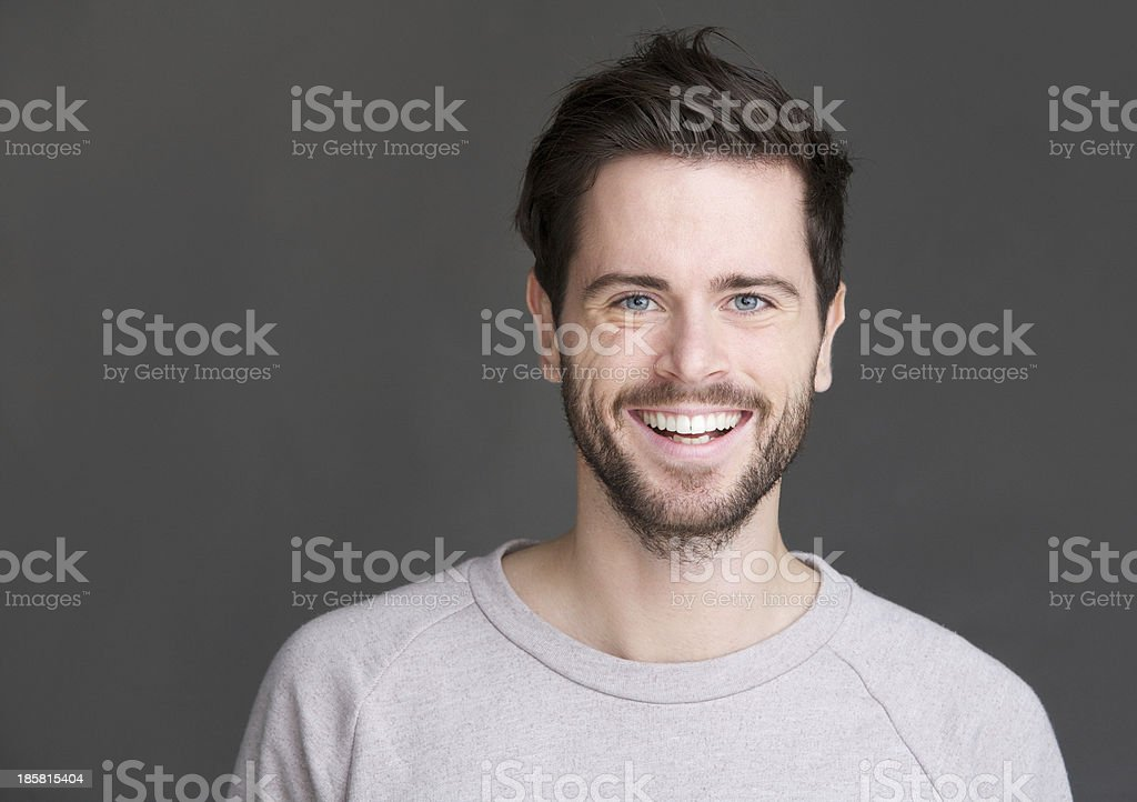 Portrait of a happy young man smiling on gray background stock photo