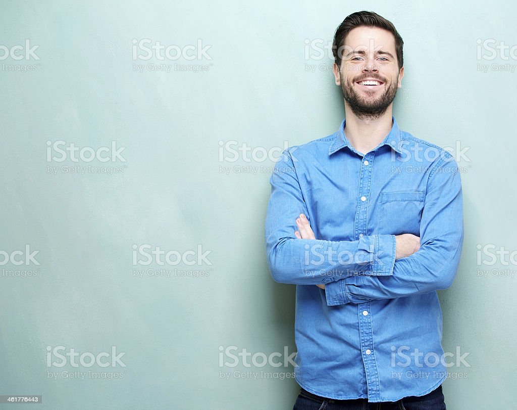 Portrait of a happy young man smiling with arms crossed stock photo