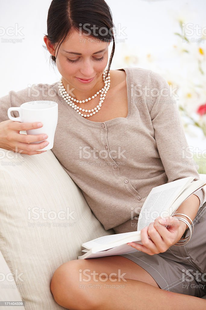 Portrait of a happy young woman reading book,on sofa royalty-free stock photo
