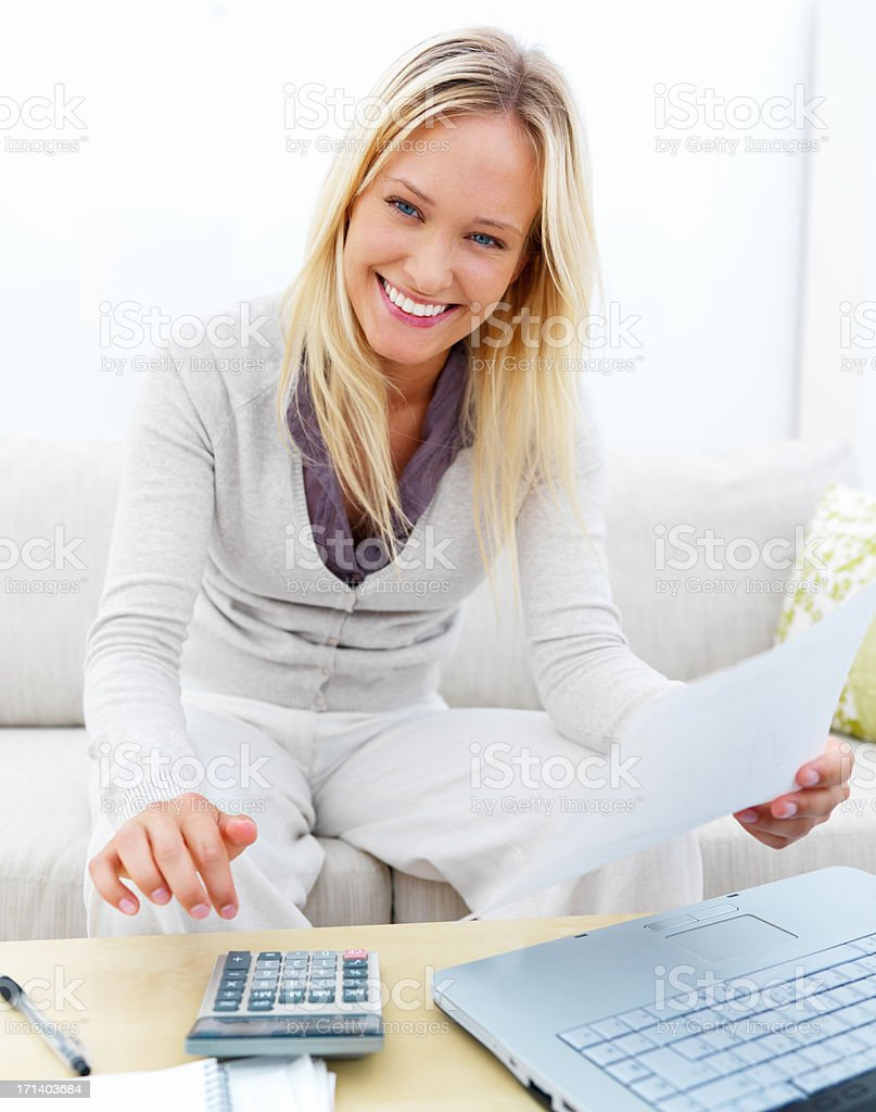 Portrait of a happy young woman sitting on sofa using laptop and calculator royalty-free stock photo