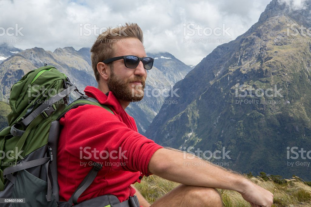 Portrait of a hiker resting on mountain top stock photo