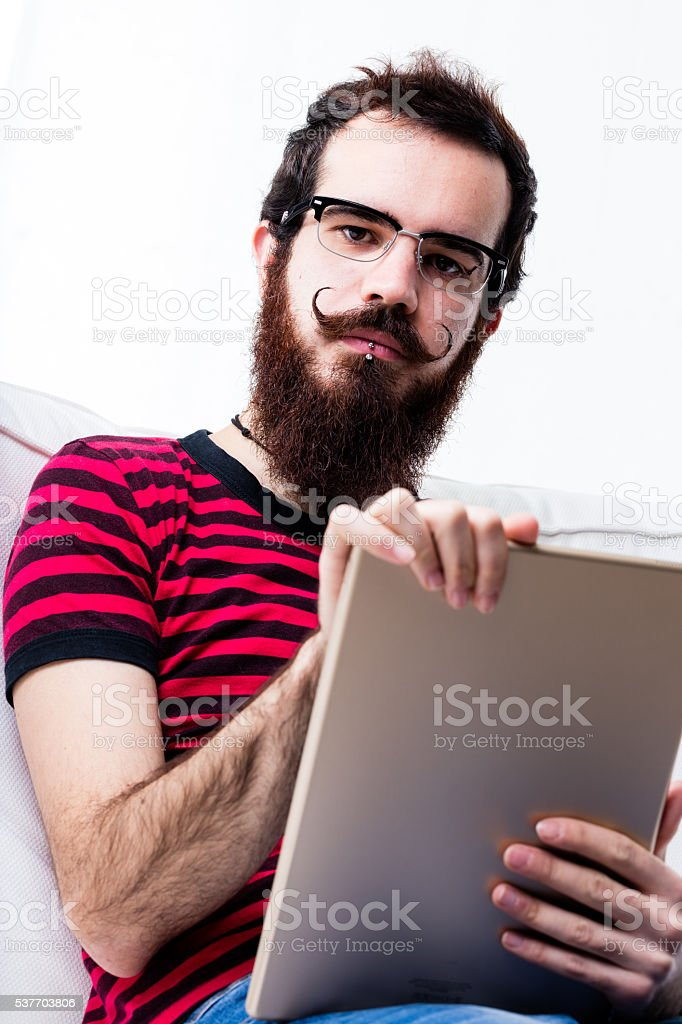 portrait of a hipster at home with his tablet stock photo