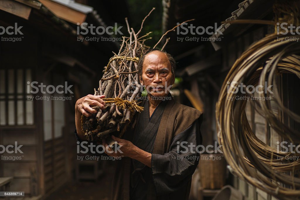 Portrait of a Japanese Man carrying a Wood Stack stock photo