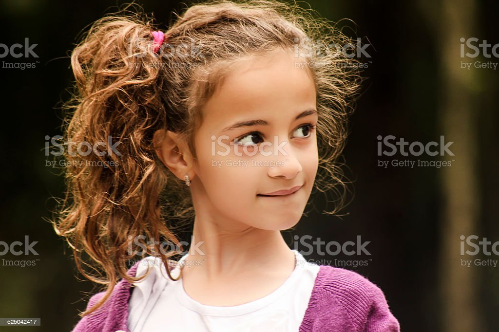 Portrait of a Little Girl Biting Her Lips stock photo