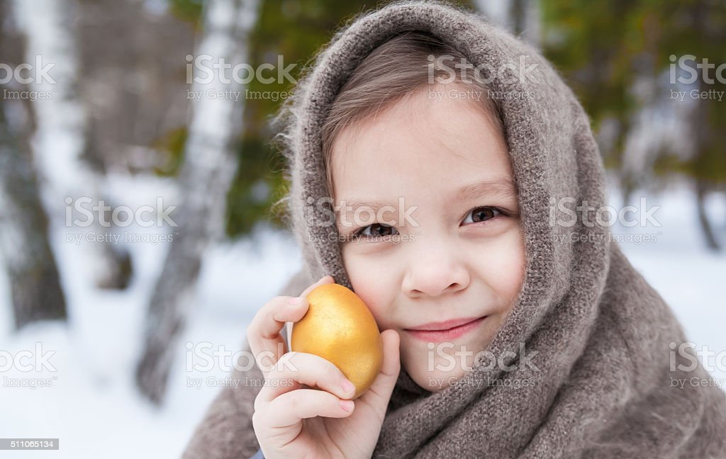 Portrait of a little girl in a shawl and a easter egg stock photo