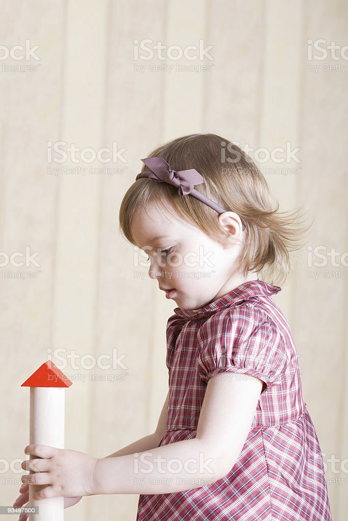 Portrait of a little girl playing with bright geometric toys stock photo