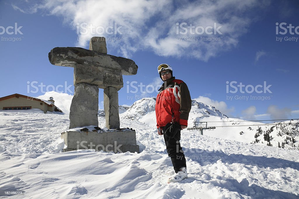 Portrait of a male skier standing next to an Inuksuk stock photo
