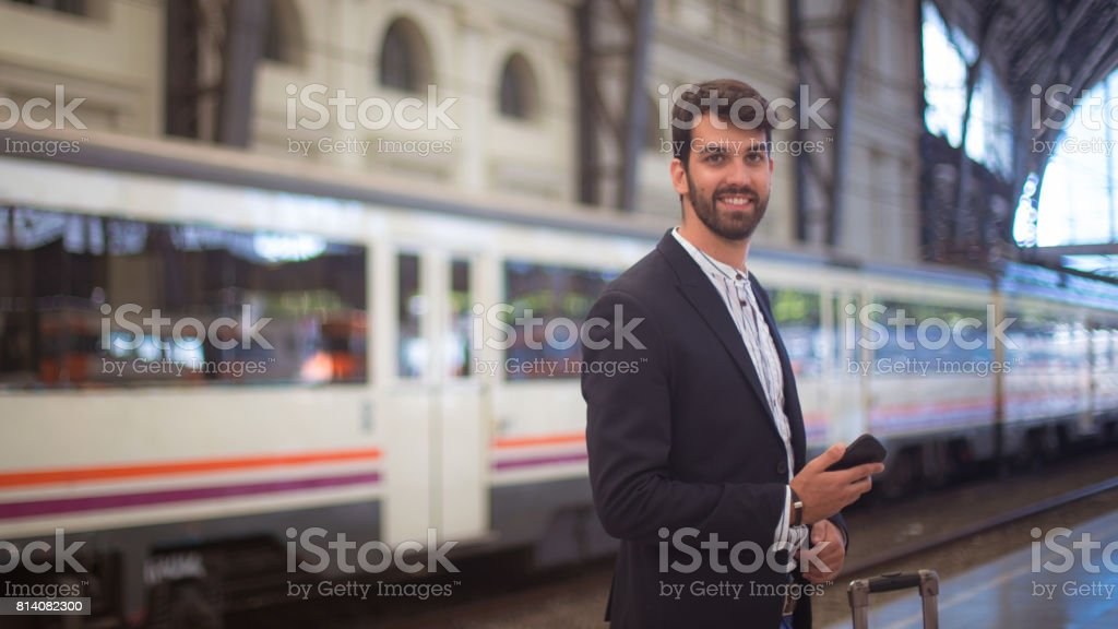 Portrait of a man holding phone at railroad station and waitining for...