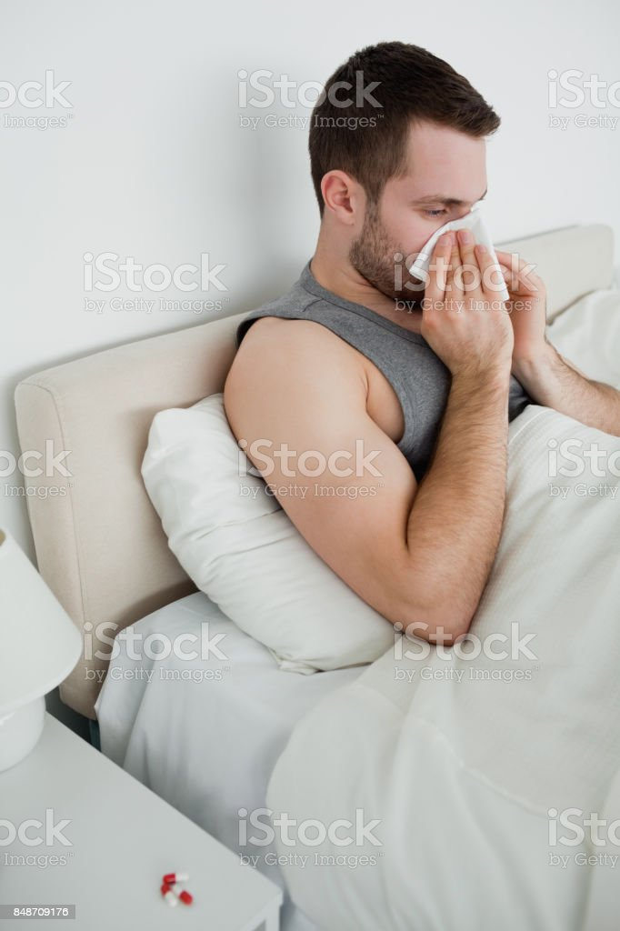 Portrait of a man blowing his nose stock photo