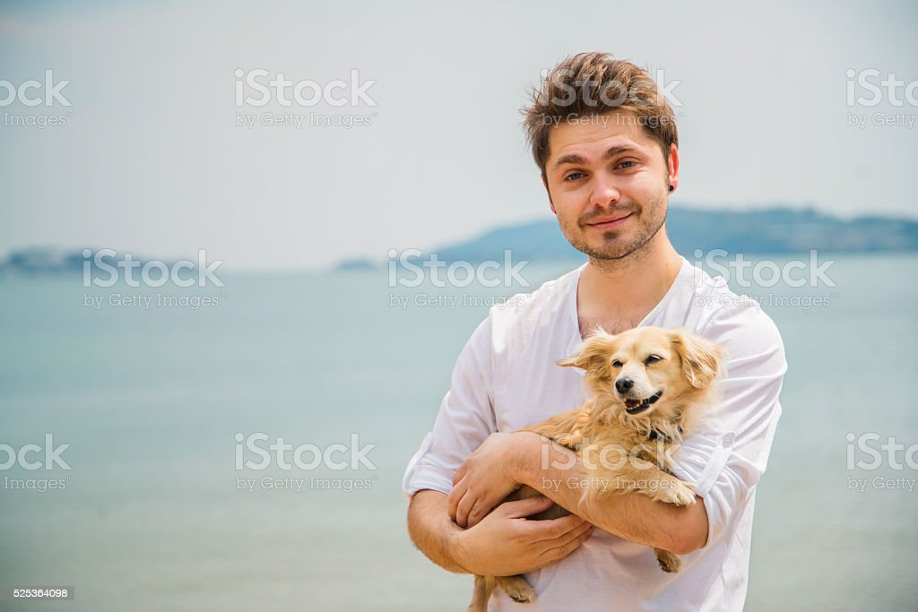 Portrait of a man holding a dog on the beach stock photo