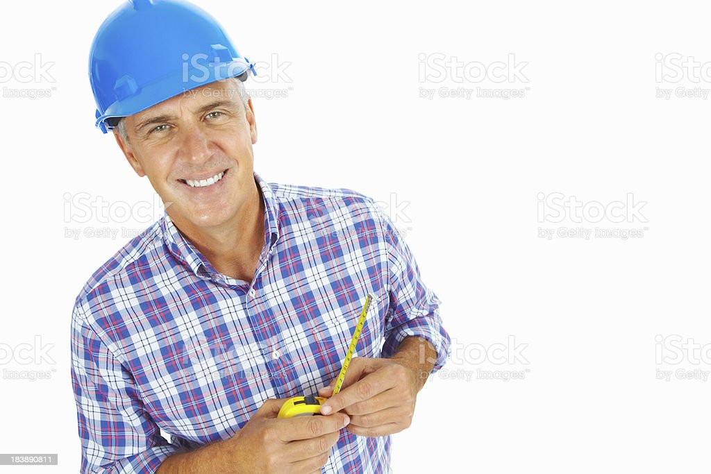 Portrait of a man in hardhat holding tape measure royalty-free stock photo