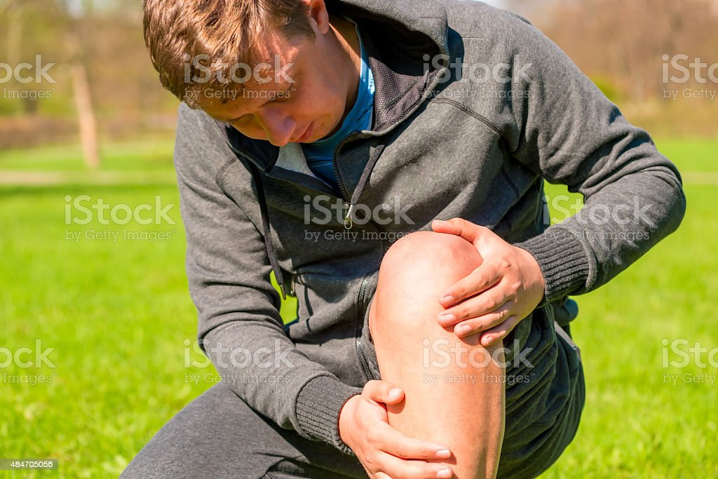 portrait of a man inspecting his injured leg stock photo