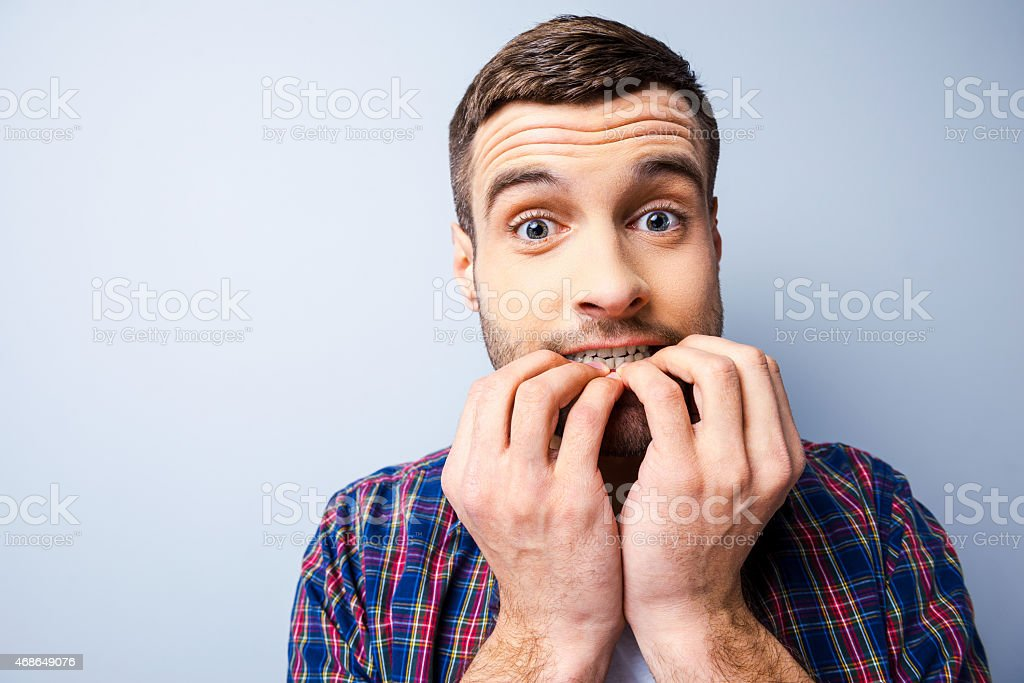 Portrait of a man playing scared biting his fingernails stock photo