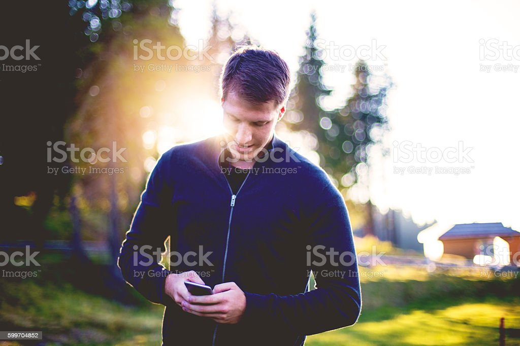 Portrait of a man, using smartphone in the middle of a forest stock photo