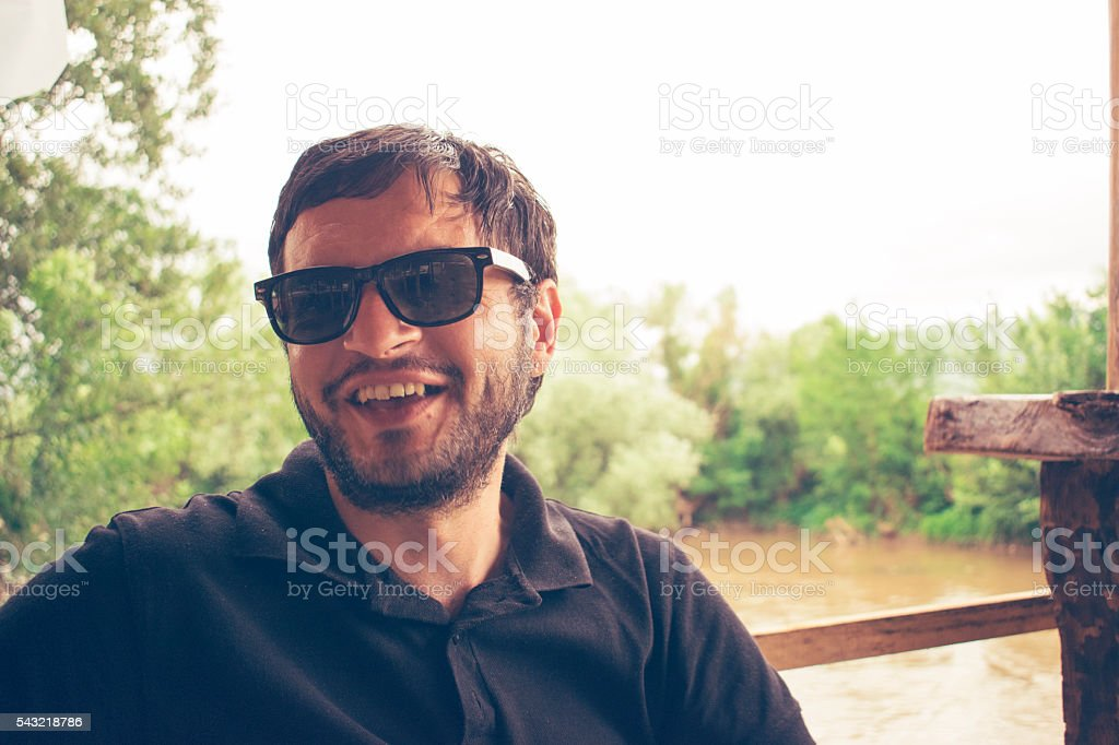 Portrait of a man wearing sunglasses and smiles. stock photo