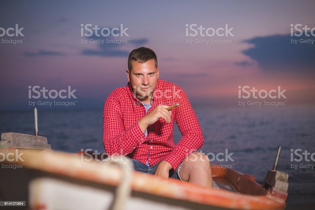 portrait of a man with a cigar on beach stock photo
